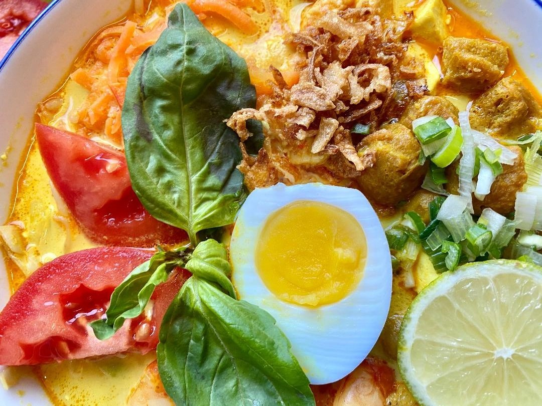 Laksa - Mixed or Vegetarian - Indonesia's spicy street soup consists of rice vermicelli, chicken, prawn, tofu and egg, served in spicy coconut milk soup + fresh tomato and basil leaves